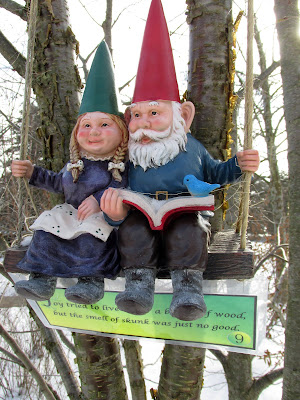 Gnome couple on a swing reading a book