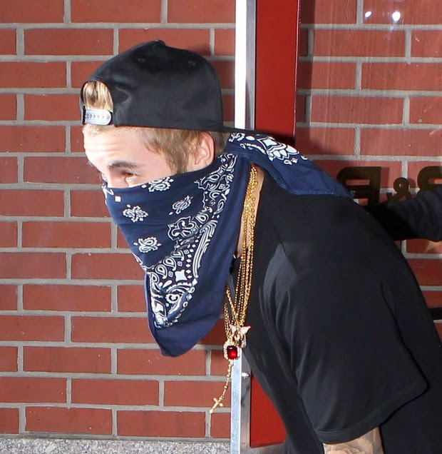 Sporting gold chains, Justin Bieber uses bandana to hide her face