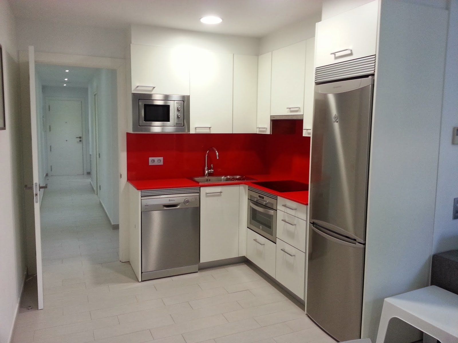 Cocina con puertas blanco brillo silestone rojo tanto en for Cocinas completas con electrodomesticos