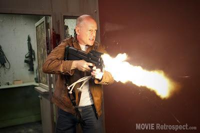 Looper - Movie Still - Bruce Willis Guns Blazing