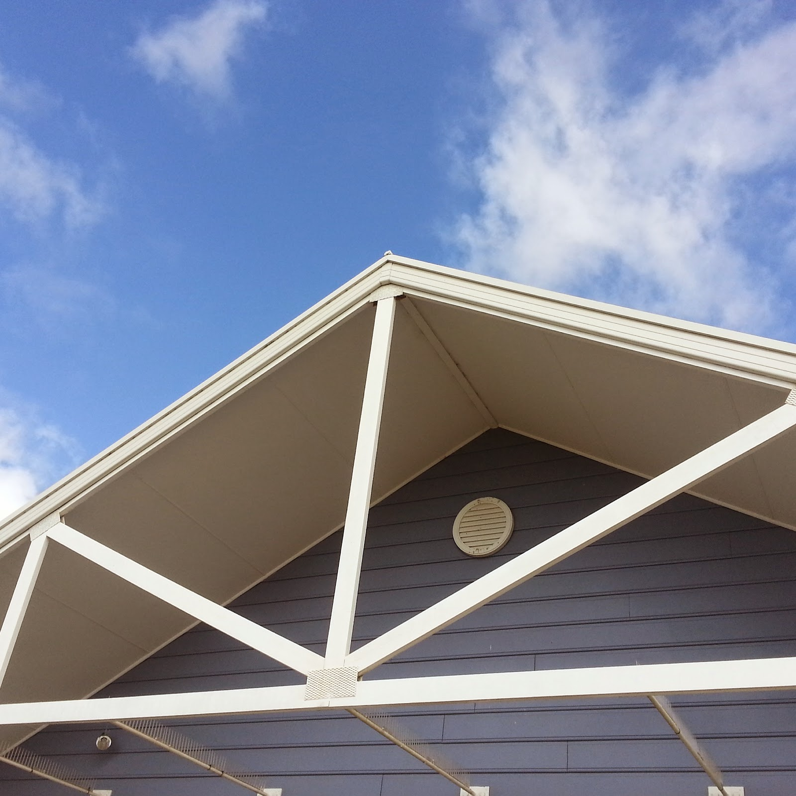 image of roof line of blue beachouse and blue skty with whispy white clouds on a sunny day