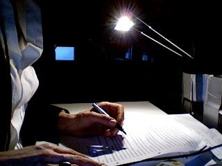 Eine Hand mit Füller in einem dunklen Kontext, in der Ferne ein Kontrollmonitor, Papier liegt auf dem Tisch, die Dolmetschkabine ist zu erahnen