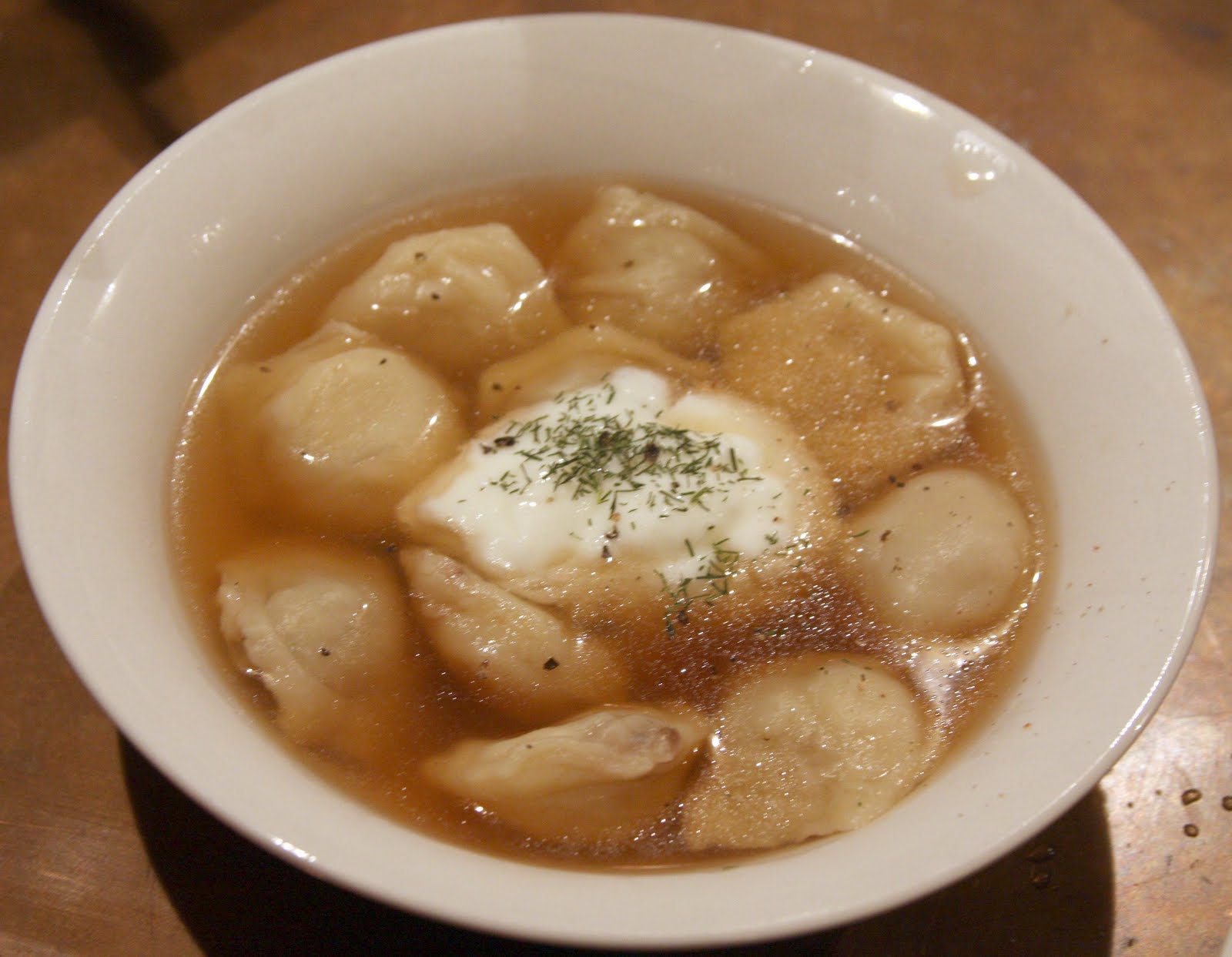 bowl of pelmeni with sour cream and dill