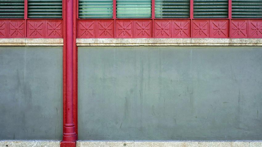 Parede ferro pintado de vermelho e cimento. Na parte de cima ranhuras de ventilação