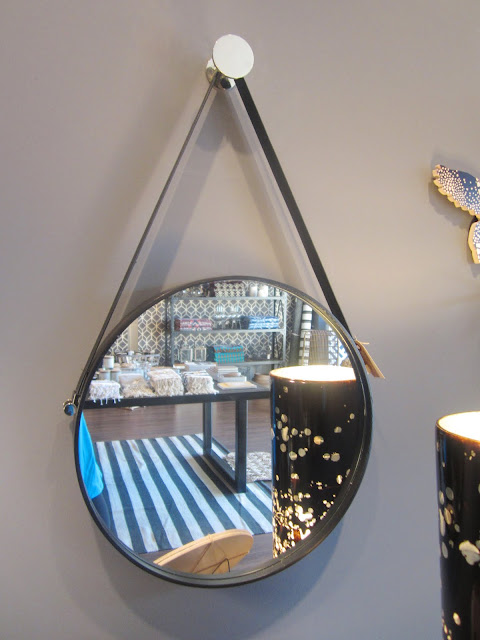 round decorative wall mirror with a leather strap