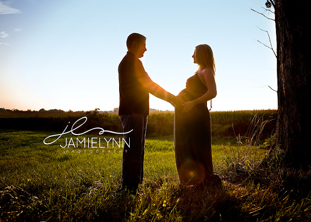 beautiful couple standing silhouetted holding pregnant belly with sunflare