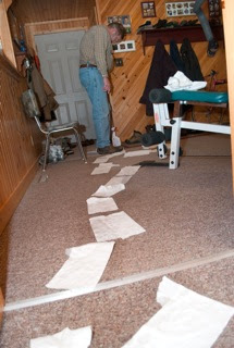 A line of white paper towel pieces lead off on a carpeted floor to a door. A man is standing sideways to the camera stepping on the papertowels.