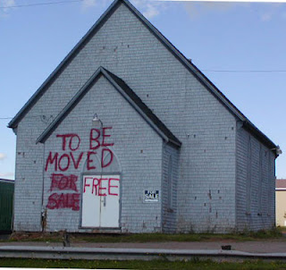 "Abandoned church for sale with crudely painted sign: ""TO BE MOVED, FOR SALE(crossed out and replaced with) FREE."""