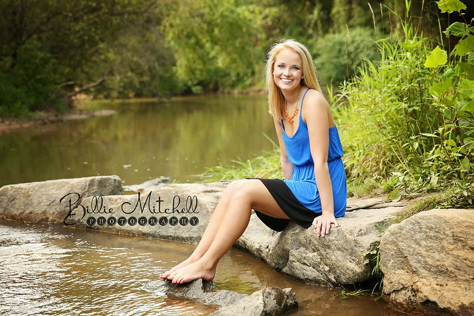 blonde senior girl in blue sundress sitting on rocks in creek