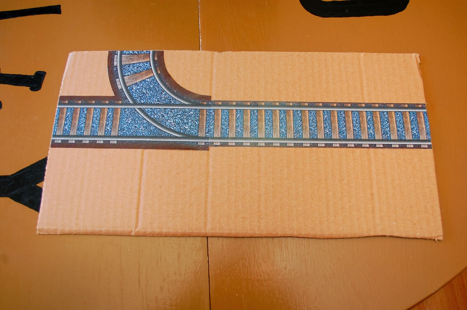 printable train tracks glued to cardboard panel