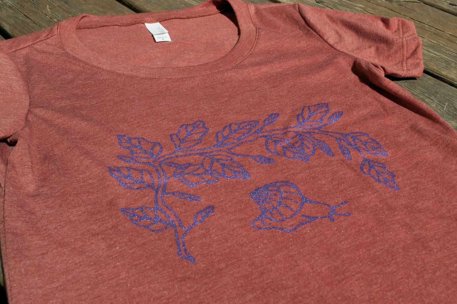 "New design ""Gastropod""/snail under a leafy branch hand printed on a light bright red, triblend women's tee."