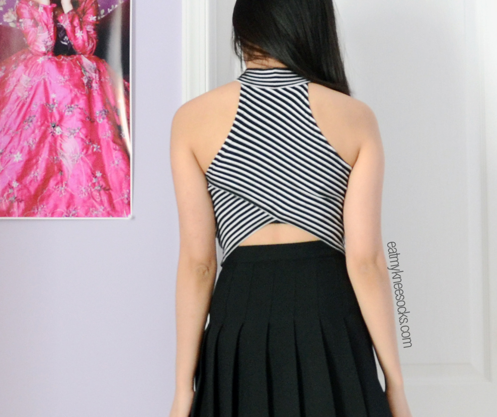 Back view of the black-and-white striped mock turtleneck crop top, with an asymmetric hemline.