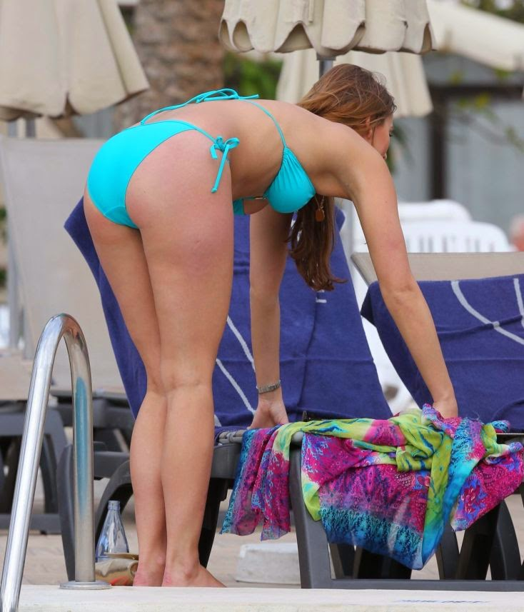 She spotted looking slender in a blue bikini while reading a magazine and soaking up the sun with a female friend on Wednesday, April 30, 2014 at Spain
