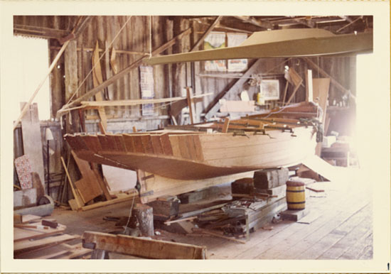 Image: 3.5 x 5 inch, color photographic print. Keel and hull view of a boat on blocks, under construction, at Grunwald's Aeolus Boat Shop.
