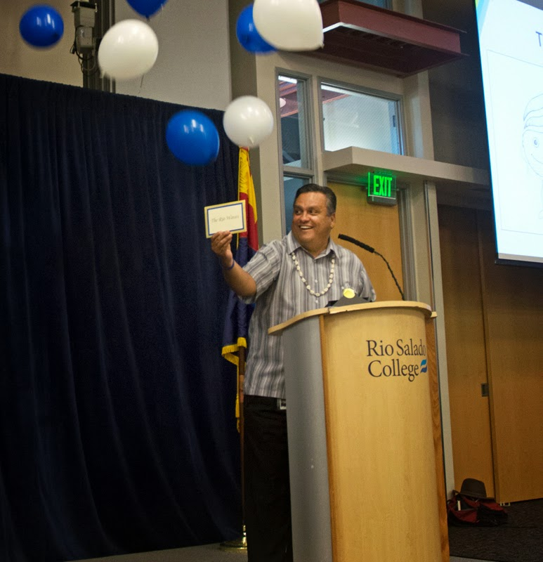 Image of Dr. Bustamante making announcement, balloons falling from cieling.