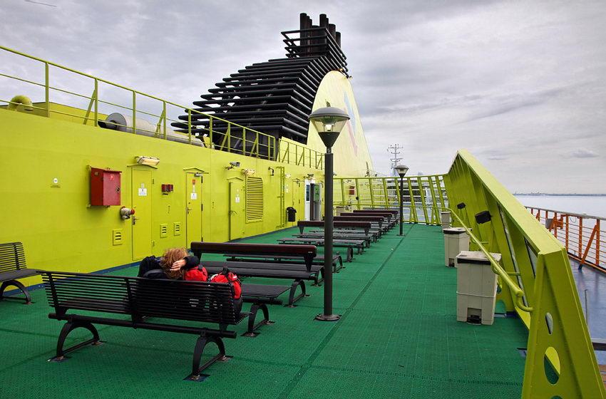 Foto da parte exterior do barco com uma fila de bancos para passageiros