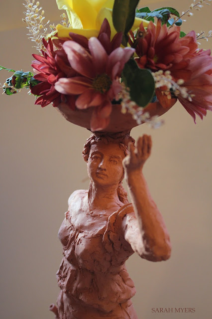 woman, sculpture, bowl, figure, terracotta, ceramic, earthenware, red, Sarah, Myers, flowers, lady, escultura, art, arte, clay, bottle, bouquet, rose, chrysanthemums, mums, yellow, orange, new, artwork, classic, figurative, renaissance, artist, tall, beautiful, spontaneous, kunst, move, walk, stride, arrangement, decor, deco, close-up, face, eyes, fingers, mouth, dress, detail