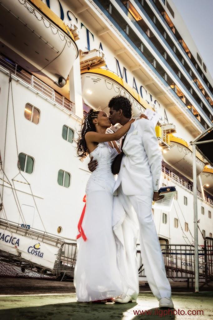 les mariés s'embrassent devant le costa magica avant de partir en croisière