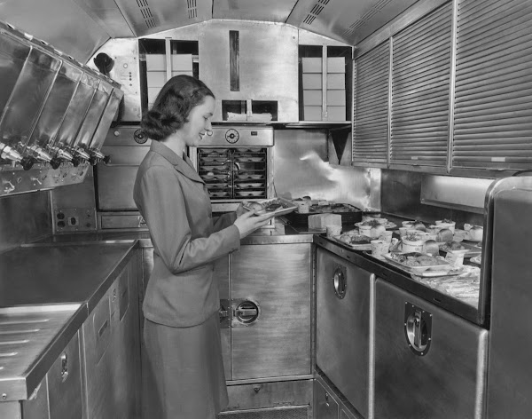A Pan American World Airways flight attendant preparing in-flight meals in the galley of an airline