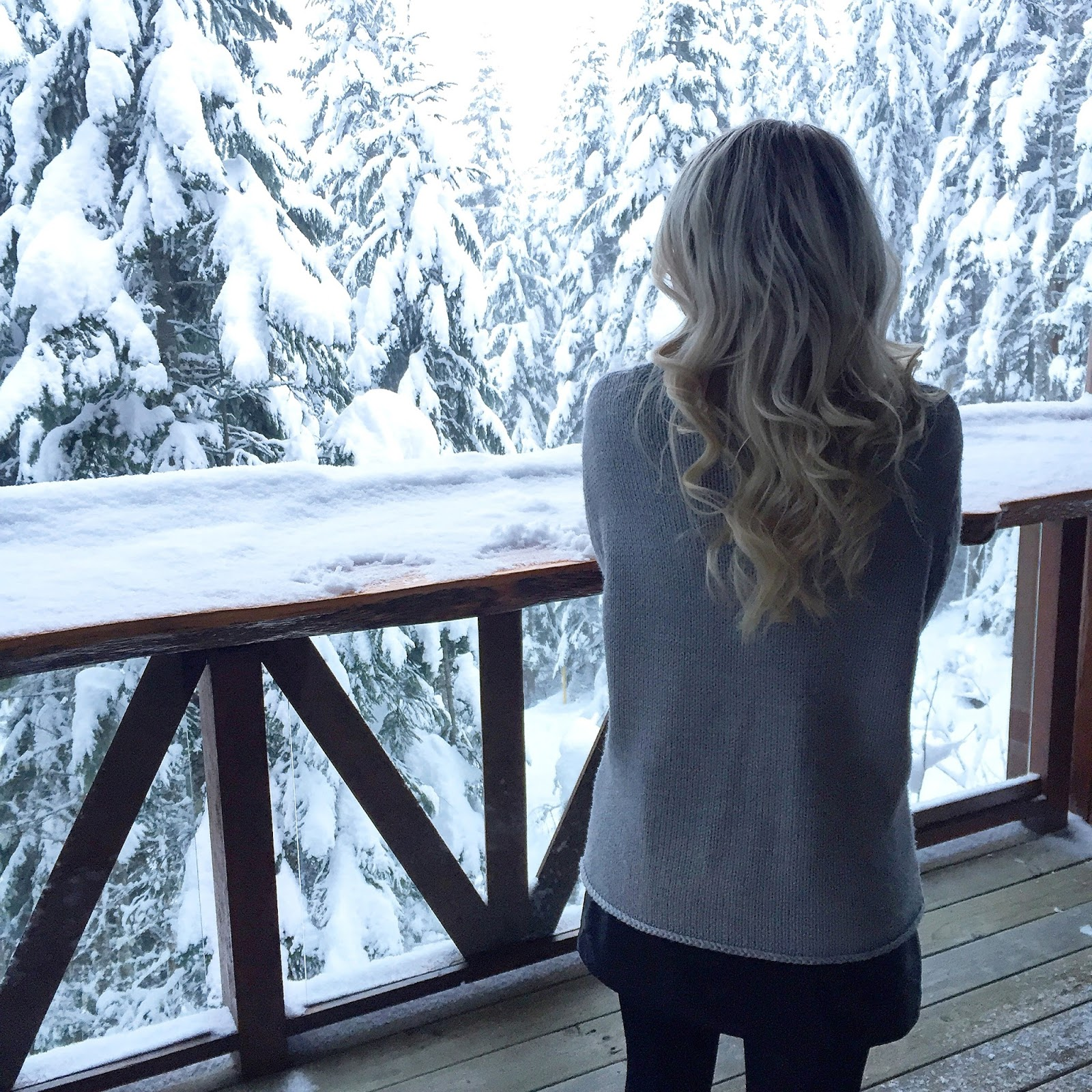 a women with loose curls and cozy knitwear stands infront of a snowy view from her balcony