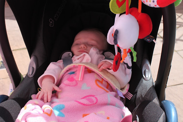 baby in pushchair with pink taggy blanket