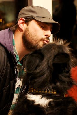 hombre besando a su perro negro