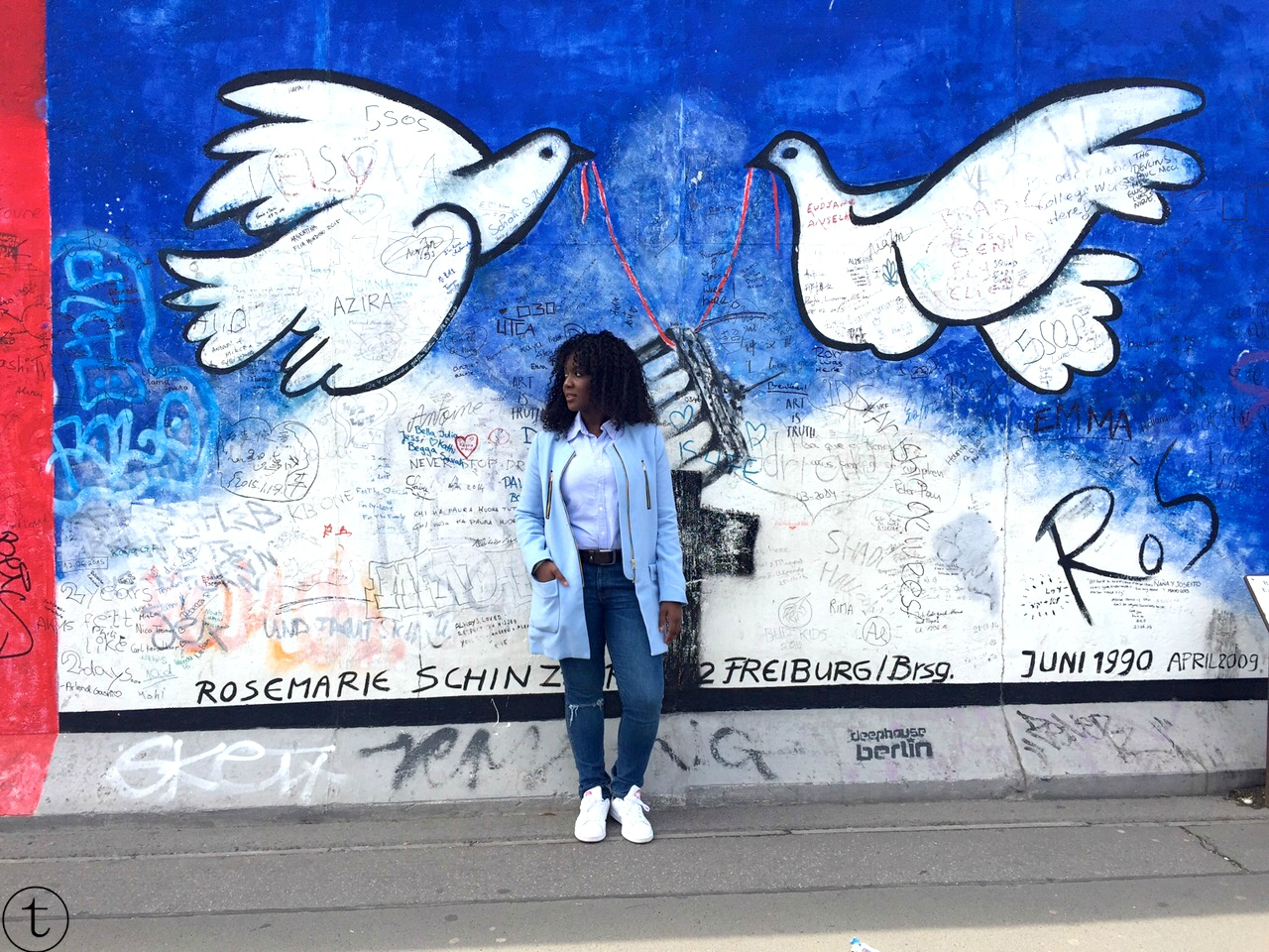 at the east side gallery wearing a blue coat and ripped jeans outfir post berlin