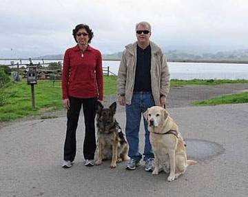 GDB graduates Aerial Gilbert with Guide Dog Splash and Ken Altenburger with Guide Dog Bristol stand together