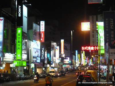 Busy Taiwanese street with a lot of neon signs and traffic