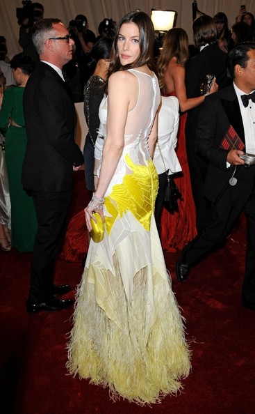 Liv Tyler in a white and yellow ombre tulle Givenchy Couture gown, with quilted and appliquéd motifs and ostrich feathers at the hem.
