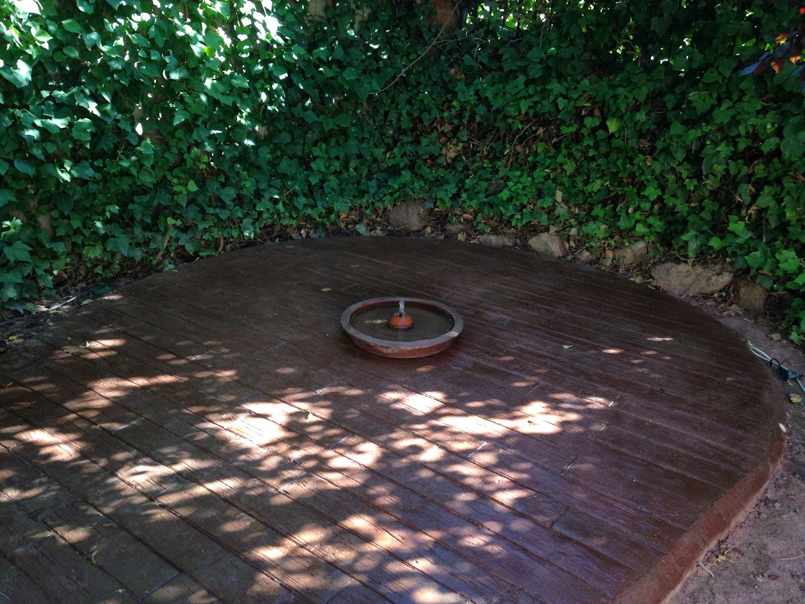 precioso rincn del jardin con el pavimento de hormign impreso en madera vieja