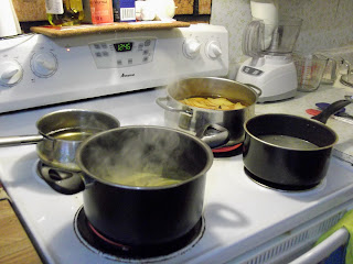 four pots on four burners of a stove