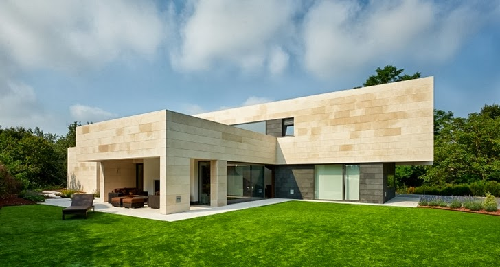 Stone facade on Modern home by Foraster Arquitectos