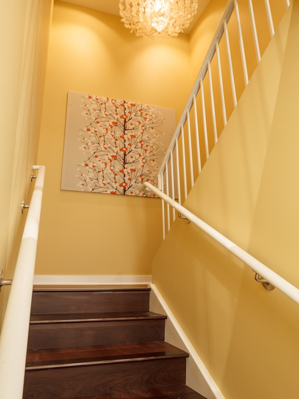 Picture of yellow walls and wooden staircase to the upper floor of duplex