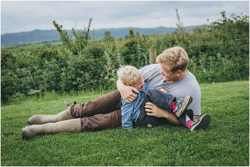 A father cuddling his son on the lawn