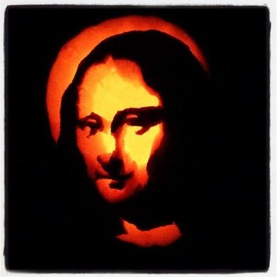 A lit pumpkin carved to look like the Mona Lisa.