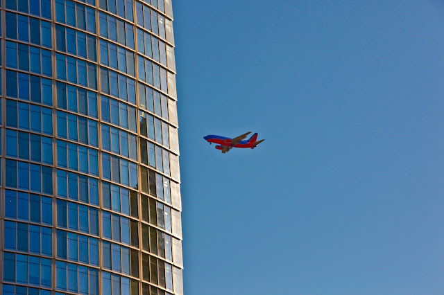 A Southwest Airlines airplane flying in the direction of a high rise in Dallas, Texas.