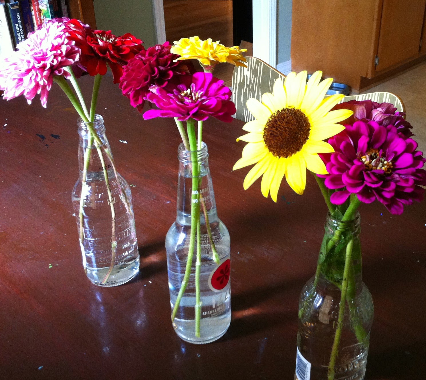 zinnias, sunflowers, fresh flowers, vases, glass bottles