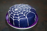 3 layer lemon cake covered with navy icing and iced with a white spiderweb