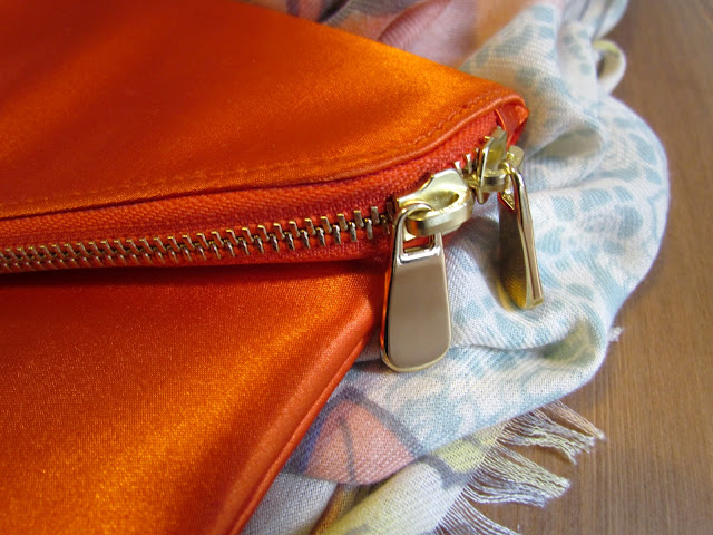 zip detail on orange satin clutch bag