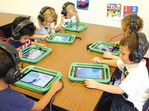 This is a picture of six kindergartens sitting around a rectangle table, doing an individual lesson on IPads. Each students has a pair of headphones on and seem to be focused on their own screens.