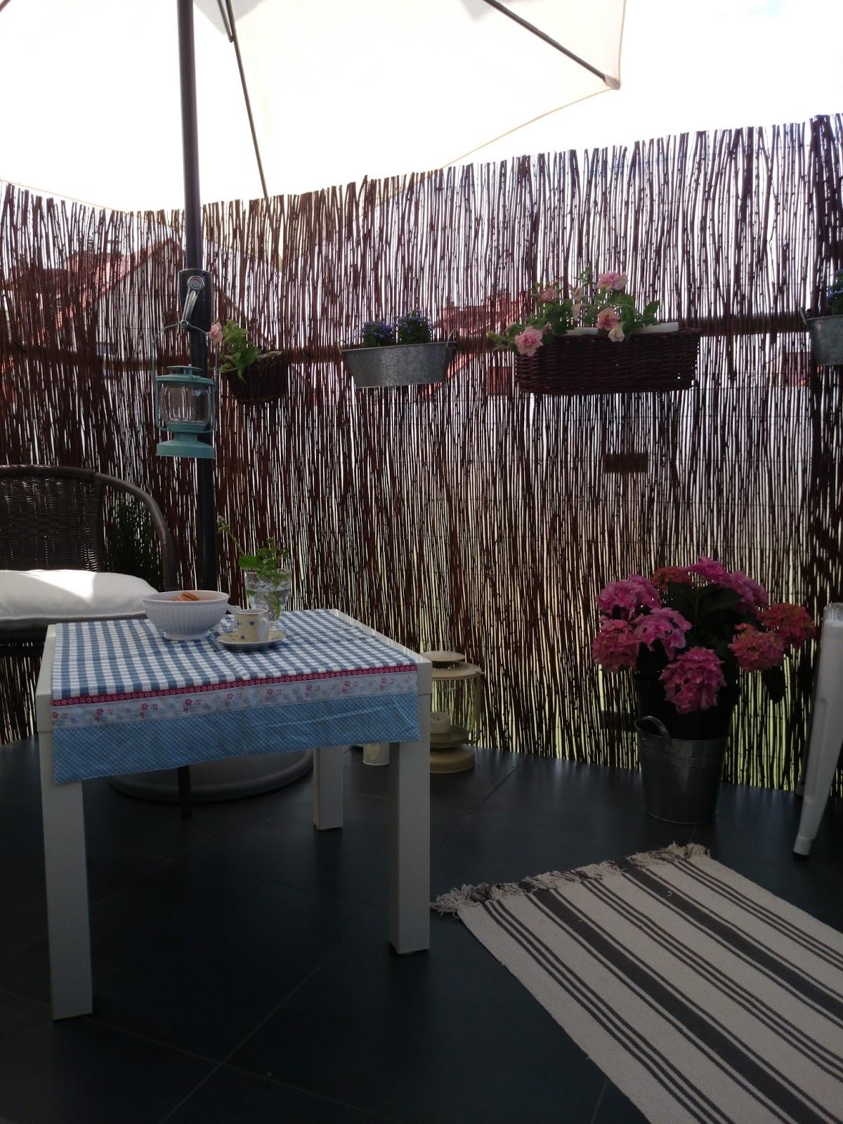 Aranżacja wiosennego balkonu, wiklinowa mata na balkonie, ściereczka Clayre & Eef, różowe hortensje na balkonie