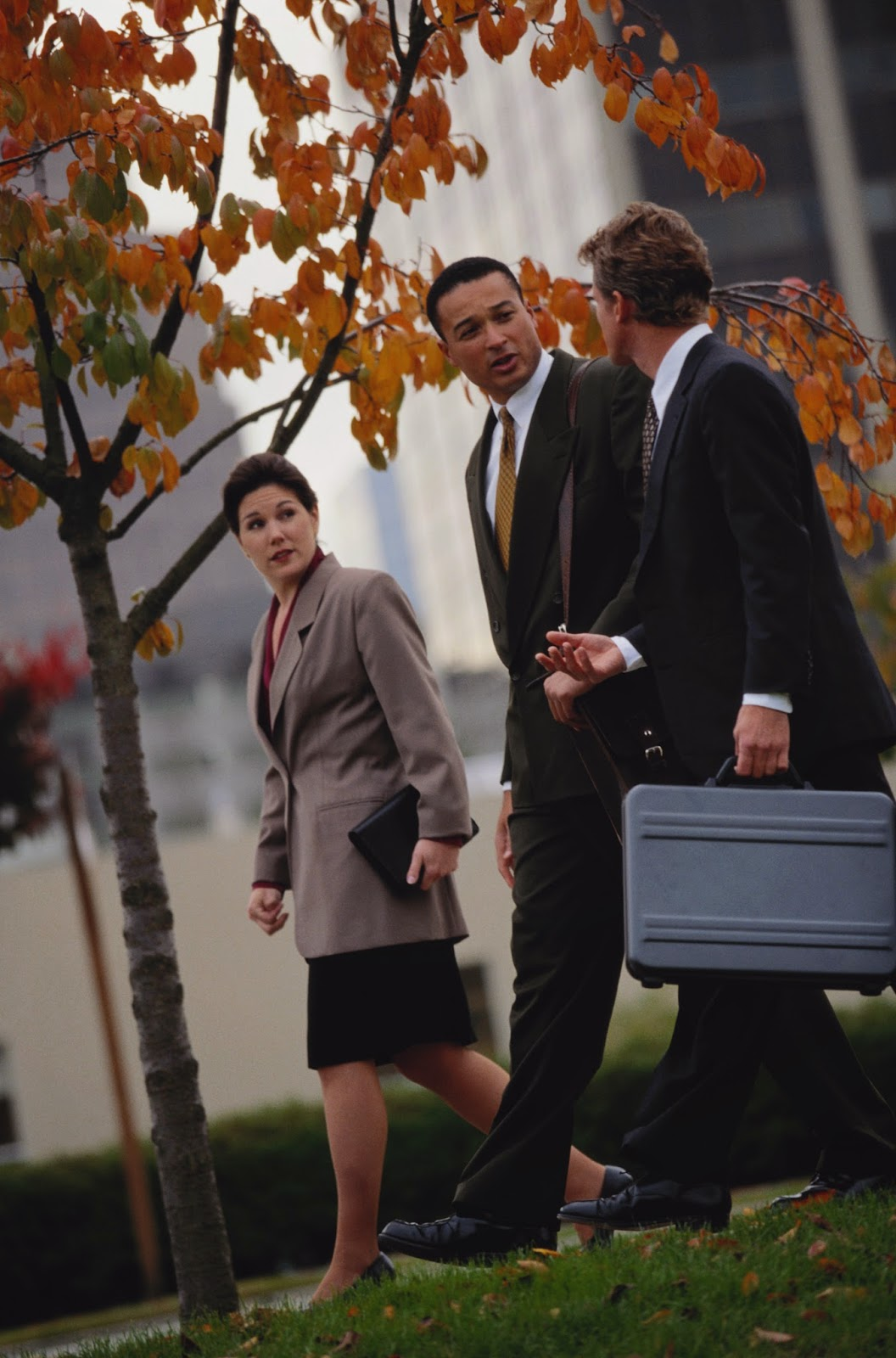 Business people walking amongst Autumn trees