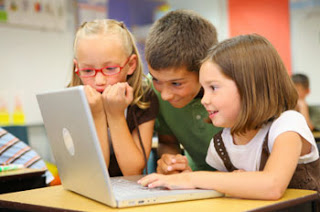 elementary students on laptop