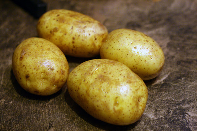 Four potatoes just washed and ready to be turned into oven baked fries.