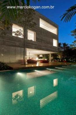 Piscina y residencia iluminadas en la noche - Casa Cubo en San Pablo, Brasil