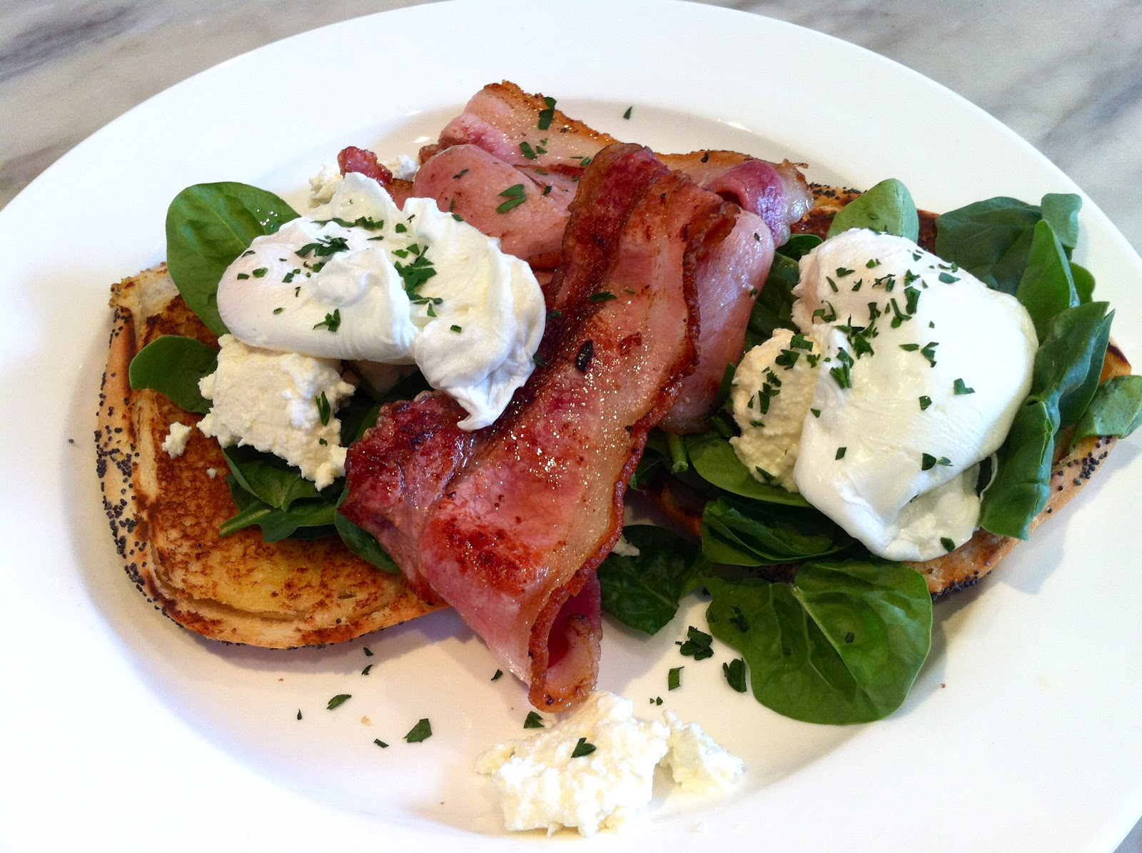This is a toasted bagel with spinach, ricotta, poached eggs and bacon ...