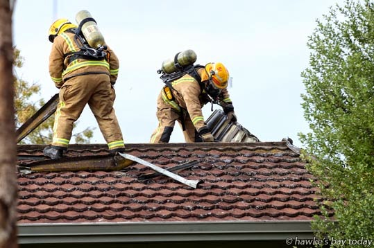 Firefighters rip up the roof looking for hotspots at a house fire in Lorne Crescent, Flaxmere, Hastings photograph