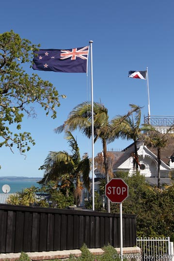 Flags fly in the windy weather in Clyde Rd, Napier. The New Zealand flag is on the property of Gerald Grocott, 1 Gladstone Rd. Red Peak is across the intersection at 18 Clyde Rd. photograph