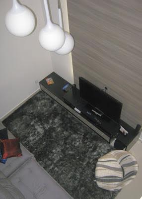 A sala de estar, conjugada com a sala de jantar, possui  pé-direito duplo, cuja visão do pavimento térreo é possível a partir do mezanino adjunto ao corpo da escada, responsável também por parte da ventilação e iluminação natural do ambiente.
